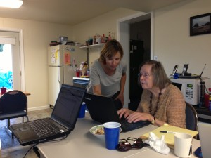 Kelly Wallace shows board member Colleen Keoski how to add a photo to her blog entry.